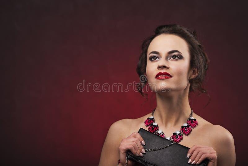 Schöne Brunettefrau mit Berufsmake-up und Frisur mit der großen Halskette, die schaut, hochhalten schwarze Handtasche lizenzfreies stockfoto