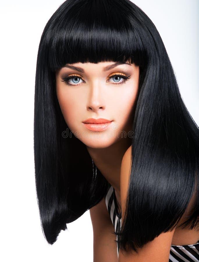 Schöne Brunettefrau mit dem langen schwarzen geraden Haar stockfoto