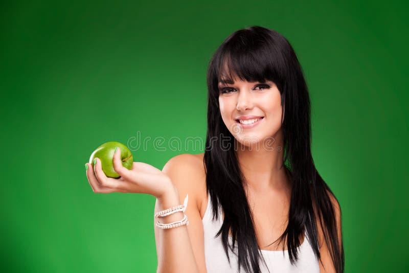 Schöne Brunettefrau mit grünem Apfel auf Grün lizenzfreies stockfoto
