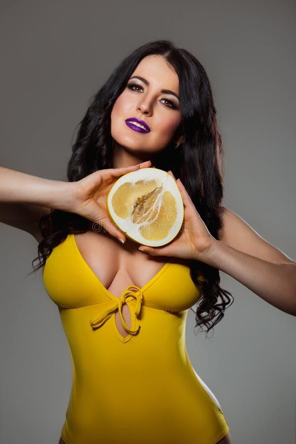 Schöne Brunettefrau mit perfektem Körper und große Brust im gelben Badeanzugbikini, der eine PampelmusenZitrusfrucht hält lizenzfreies stockbild