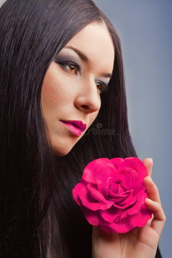 Schöne Brunettefrau mit Rosa stieg stockfotos