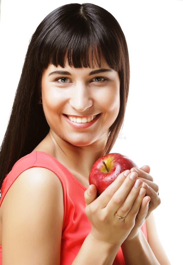Schöne Brunettefrau mit rotem Apfel in den Händen lizenzfreie stockbilder