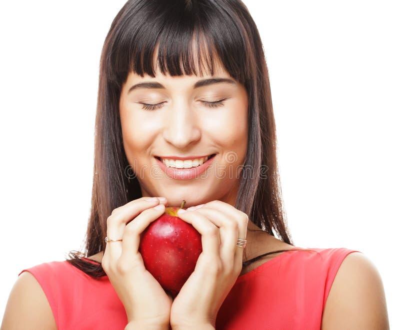 Schöne Brunettefrau mit rotem Apfel in den Händen stockbild