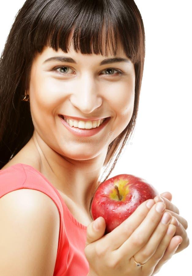 Schöne Brunettefrau mit rotem Apfel in den Händen stockfotos