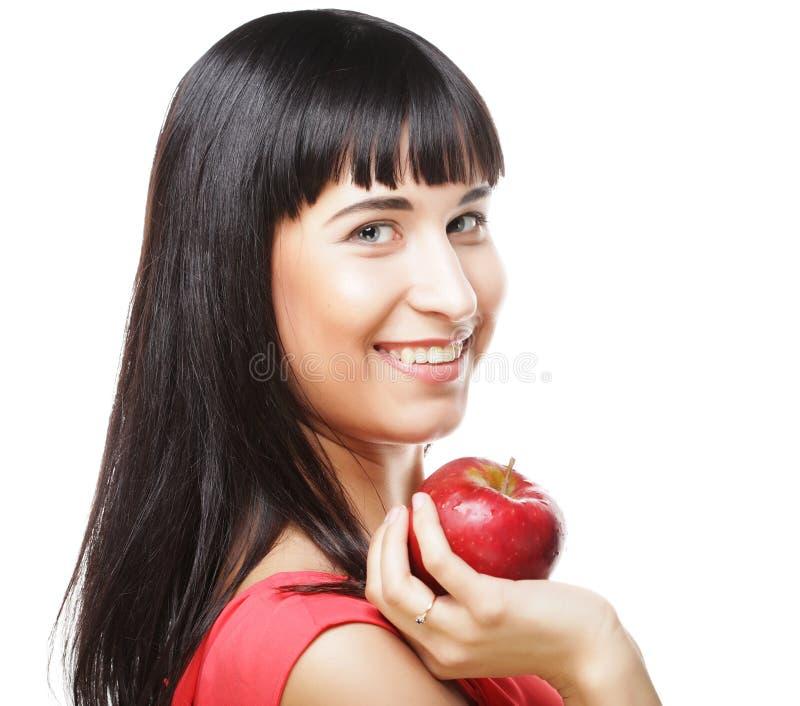 Schöne Brunettefrau mit rotem Apfel in den Händen lizenzfreies stockfoto