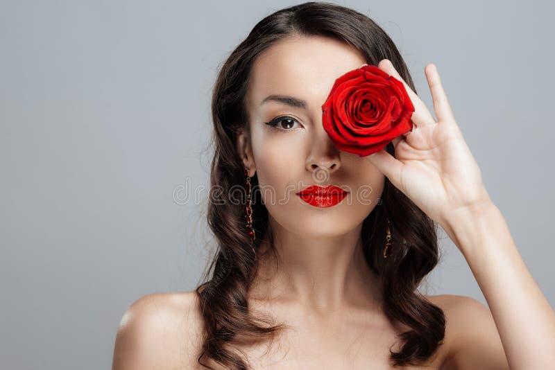 Schöne Brunettefrau mit rotem Lippenstift auf Lippen Nahaufnahmemädchen mit stieg lizenzfreies stockbild
