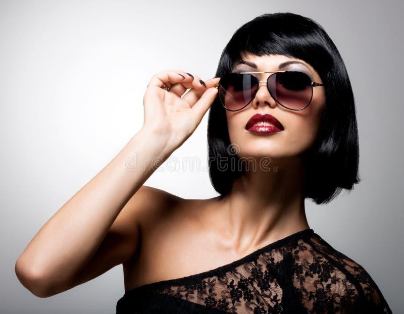 Schöne Brunettefrau mit Schussfrisur mit roter Sonnenbrille lizenzfreies stockfoto