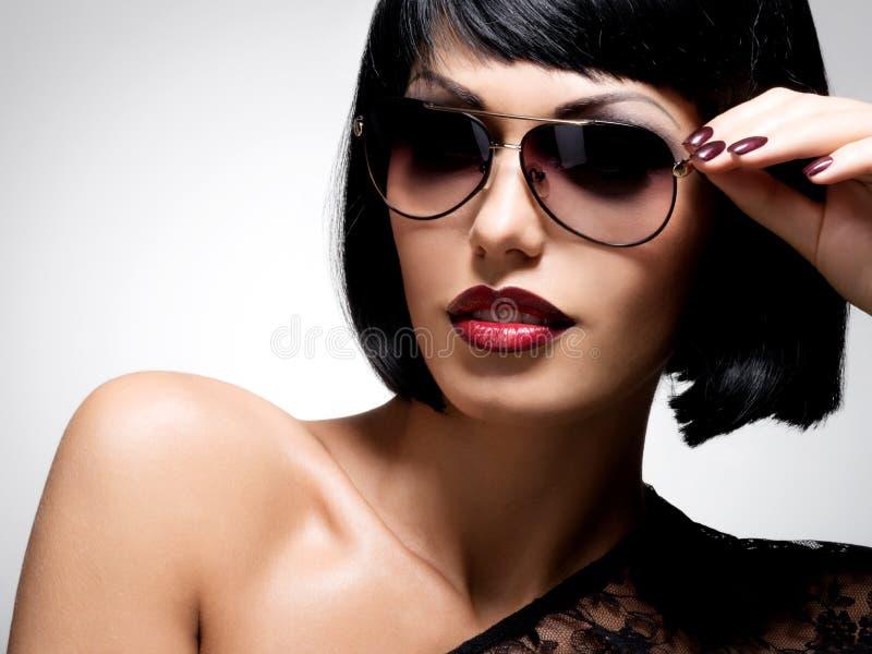 Schöne Brunettefrau mit Schussfrisur mit roter Sonnenbrille stockfoto