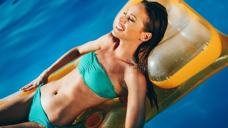 Schöne Brunetteschwimmen im Pool lizenzfreie stockbilder