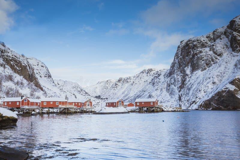 schöne Bucht im Meer mit kleinen roten Häusern auf der Küste, Winterzeit mit Hochgebirge lizenzfreie stockbilder