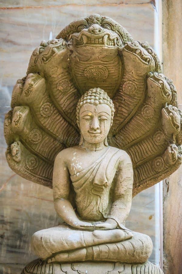 Schöne Buddha-Statue gemacht vom Sandstein und -abdeckung mit Nagaköpfen Stein-Buddha-Statue mit sieben Phaya-Naga geht voran Sto lizenzfreies stockfoto