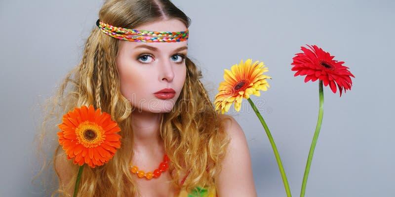 Schöne bunte Blumen der jungen Frau lizenzfreies stockbild