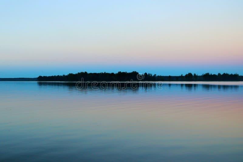 Schöne bunte Herbstlandschaft mit einem See und einem Sonnenunterganghimmel Ungewöhnliches Wetterphänomen lizenzfreie stockfotos