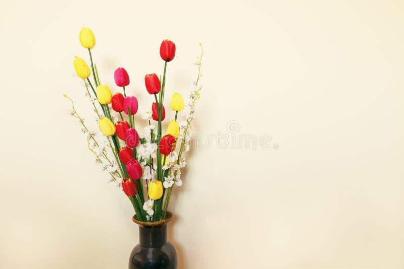 schöne bunte künstliche Blumen auf Betonmauer lizenzfreies stockfoto