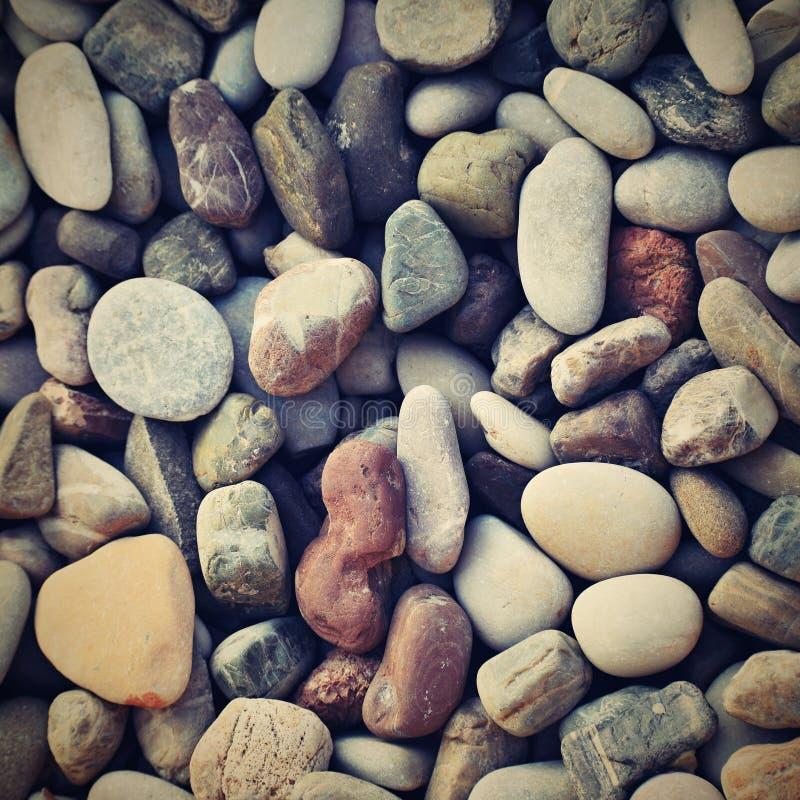 Schöne bunte Steine durch das Meer auf dem Strand lizenzfreies stockbild