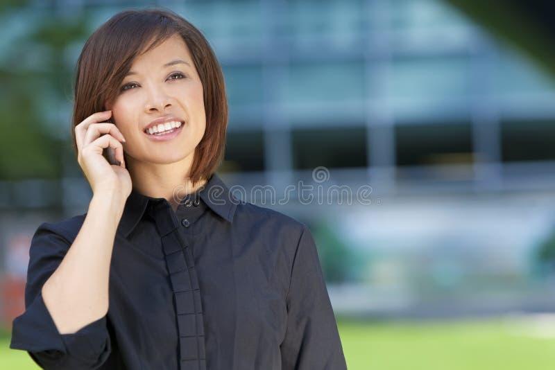 Schöne chinesische asiatische Frau auf ihrem Handy lizenzfreies stockbild