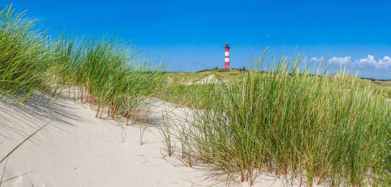 Schöne Dünenlandschaft mit traditionellem Leuchtturm an Nordse stockfoto