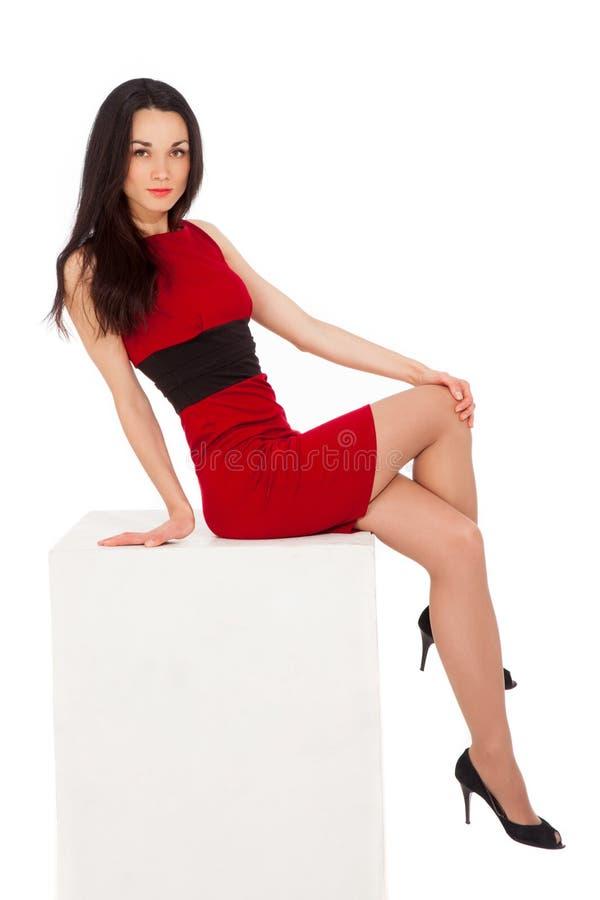 Schöne dünne Brunettefrau im roten Kleid, das auf Würfel sitzt stockfotografie