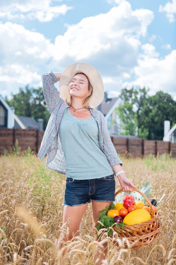 Schöne dünne Frau, die frei und bei der Stellung auf dem Weizengebiet ruhig sich fühlt lizenzfreie stockfotos