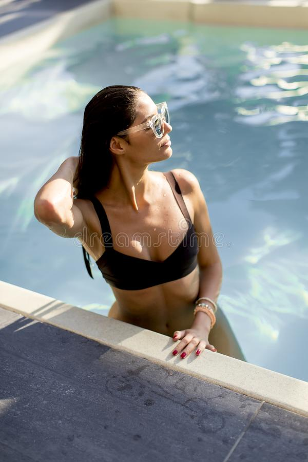 Sch?ne d?nne Frau im Bikini und in Sonnenbrille, die auf Poolside eines Swimmingpools sich entspannen und ein Sonnenbad nehmen stockfotos