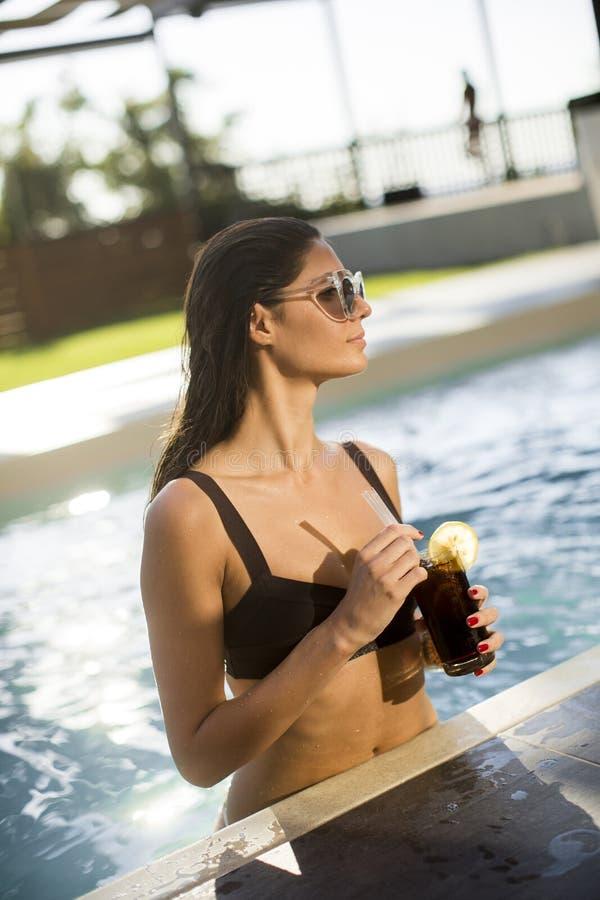 Sch?ne d?nne Frau im Bikini und in Sonnenbrille, die sich entspannen und im Getr?nkcocktail auf Poolside eines Swimmingpools stockfotos