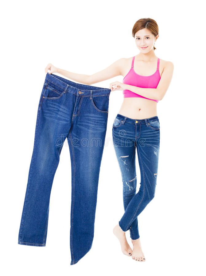 Schöne dünne junge Frau mit großen Jeans stockbild