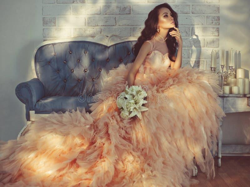 Schöne Dame in den herrlichen Couturen kleiden auf Sofa an lizenzfreie stockbilder