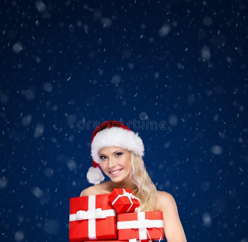 Schöne Dame in der Weihnachtskappe hält einen Satz Geschenke stockfoto