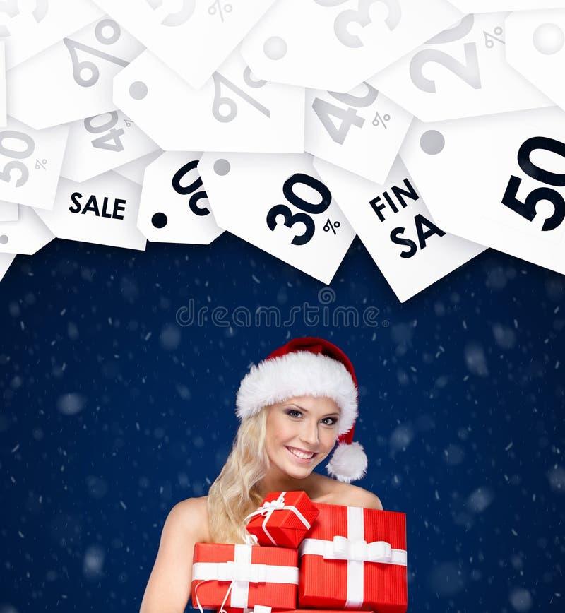 Schöne Dame in der Weihnachtskappe hält einen Satz Geschenke für Freunde stockbild