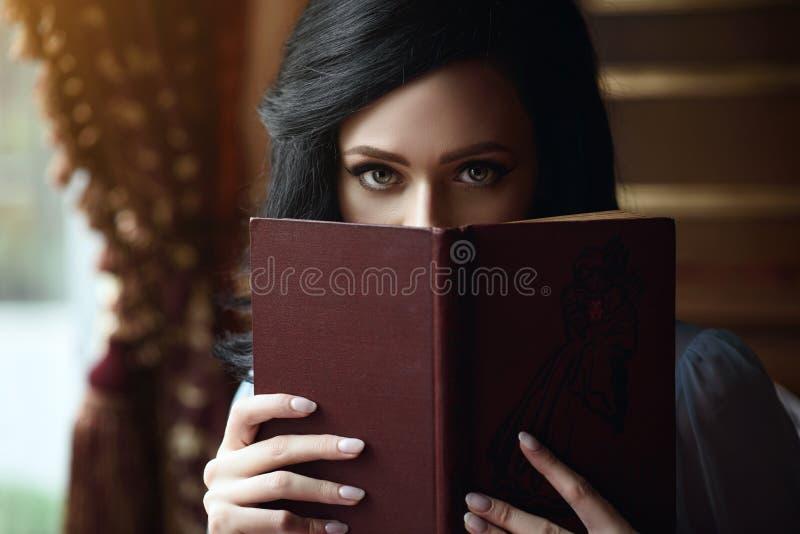 Schöne Dame, die das Teil ihres Gesichtes hinter dem offenen Buch versteckt stockfoto