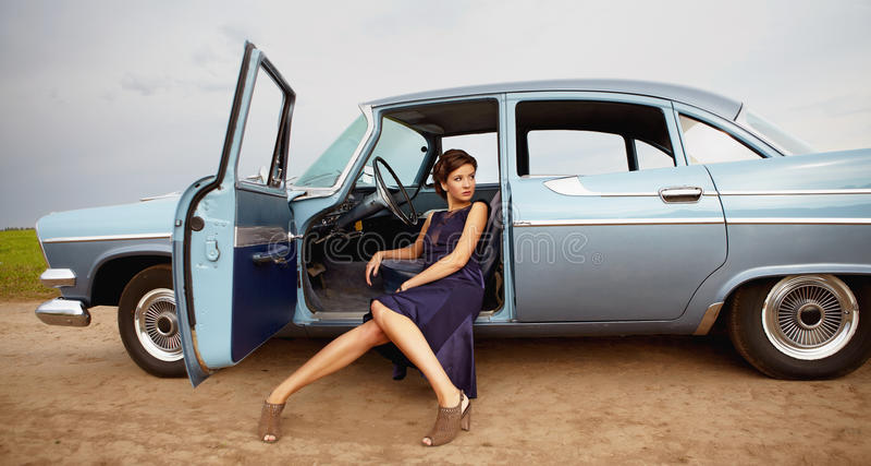 Schöne Dame, die in einem Retro- Auto sitzt stockbilder
