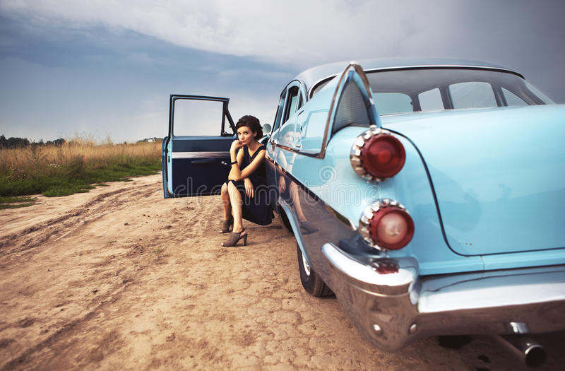 Schöne Dame, die in einem Retro- Auto sitzt stockfotos