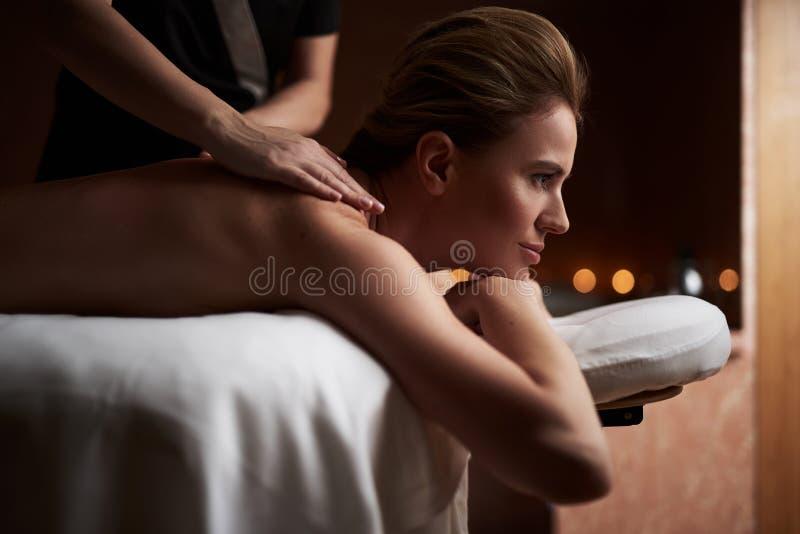 Schöne Dame, die Massage im Badekurortsalon hat stockfoto