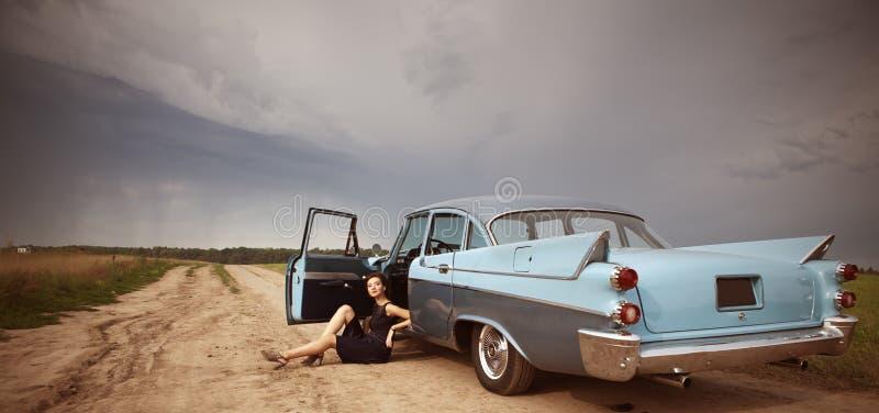 Schöne Dame, die nahe Retro- Auto steht stockbilder