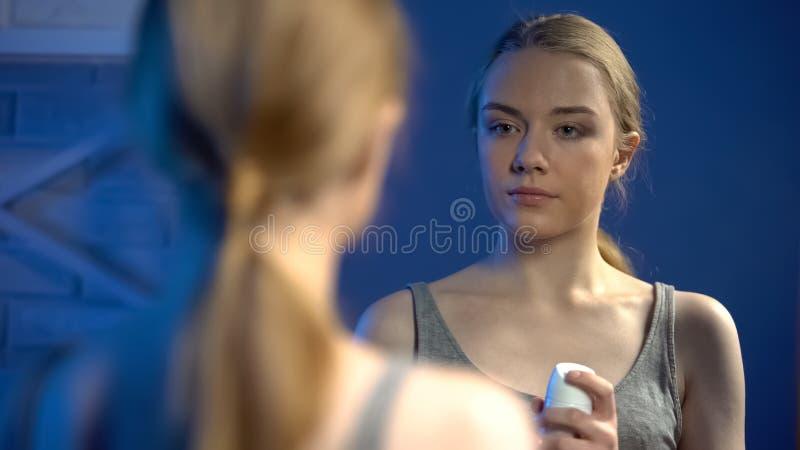 Schöne Dame, die Spraydesodorierendes mittel vor Spiegel, persönliche Hygiene hält lizenzfreie stockfotos