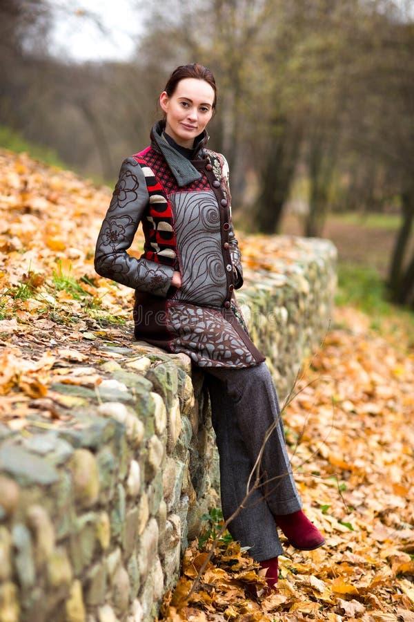 Schöne Dame im bunten Mantel wirft im Herbst auf stockbilder