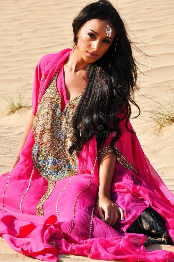 Schöne Dame im rosafarbenen Kleid in der Wüste lizenzfreie stockbilder