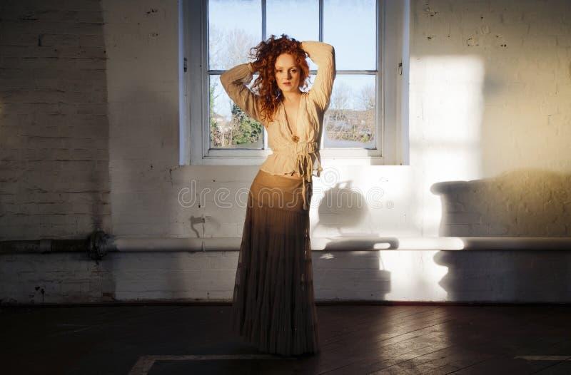 Schöne Dame mit der Kaskade des langen gewellten roten Haares, Hand, die Haar auf ihren Kopf hält lizenzfreie stockbilder
