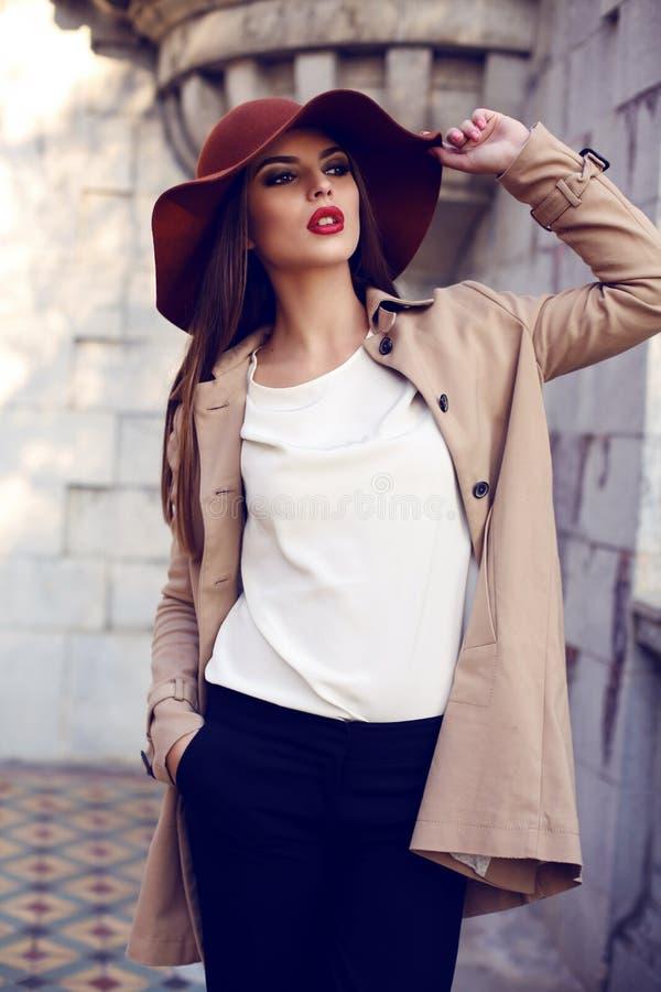Schöne damenhafte Frau in der eleganten Kleidung, die im Herbstpark aufwirft stockbild