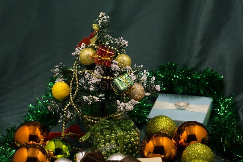 Schöne Dekorationen um den Weihnachtsbaum Weihnachtsbaum, glückliches neues Godemichet über goldene Spielwaren, Ballone, Blumen, stockfoto
