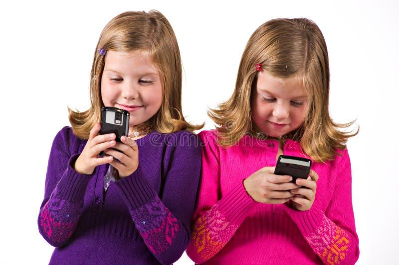 Schöne Doppelmädchen-Versenden von SMS-Nachrichten stockfotos