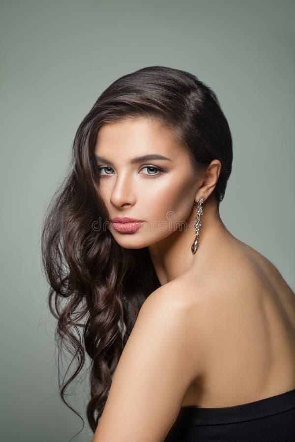 Schöne dunkelbraune Haarfrau Mode-Modell mit langer perfekter Frisur, Make-up und Schmuckohrringen lizenzfreies stockbild