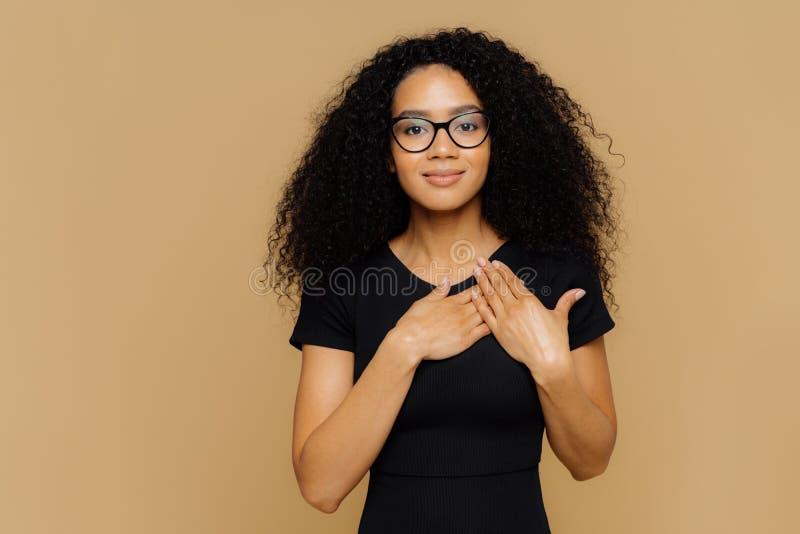 Schöne dunkelhäutige Frau hält Palmen nahe hören, ausdrücken Dankbarkeit, Dankbarkeit, hat freundlichen Gesichtsausdruck, trägt lizenzfreies stockbild