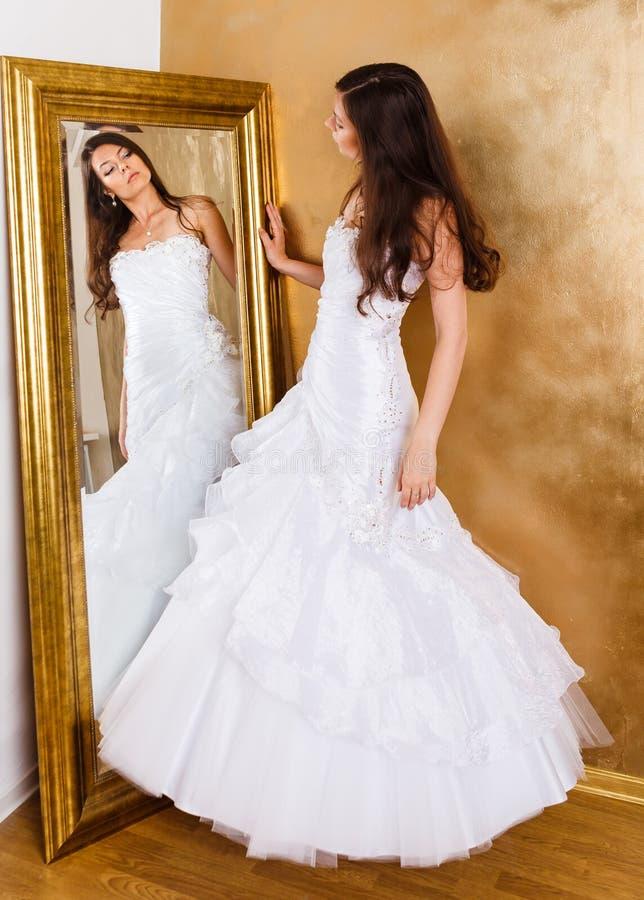 Schöne dunkelhaarige Frau in weißem Brautkleid lizenzfreie stockfotos