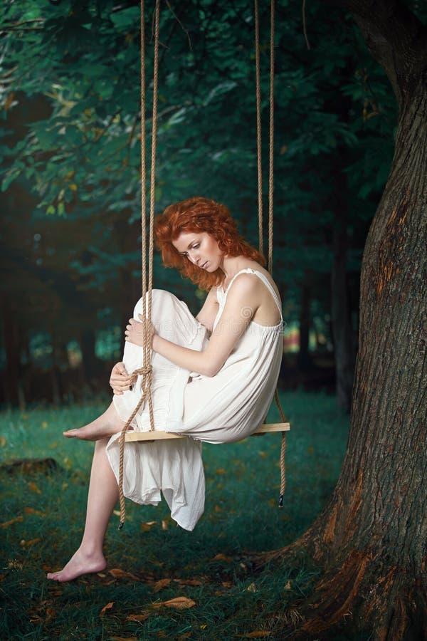 Schöne durchdachte Frau auf einem Schwingen lizenzfreie stockbilder