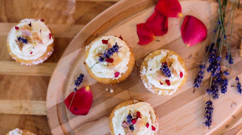 Schöne Ebenenlage der Sommerkleinen kuchen von Blumenkleinen kuchen auf hölzernem Behälter mit Lavendelblumen und den roten rosaf stockbild