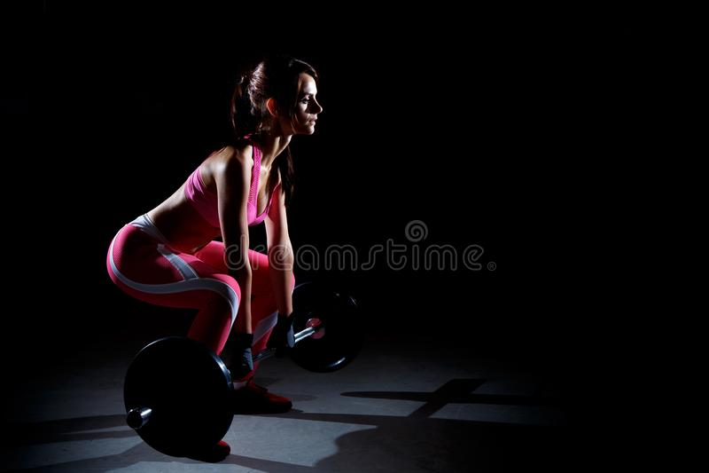 Schöne Eignungsfrau, die Hocken mit einem Barbell tut Schattenbild der Sportfrau auf einem schwarzen Hintergrund lizenzfreie stockfotos