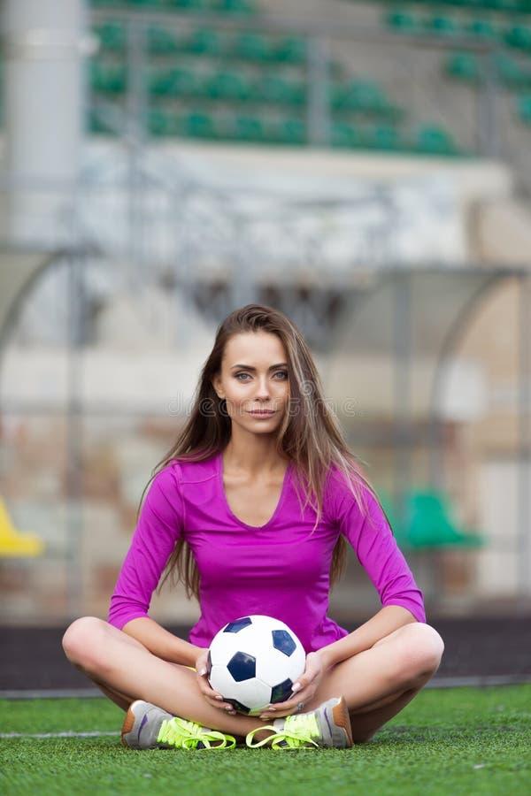 Schöne Eignungsfrau oder -cheerleader mit einem Fußball lizenzfreie stockbilder
