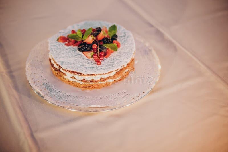 Schöne einfache Hochzeitstorte mit Früchten auf Tabelle am Hochzeitsempfang draußen am Abend Köstliche kleine Hochzeitstorte here lizenzfreie stockfotos