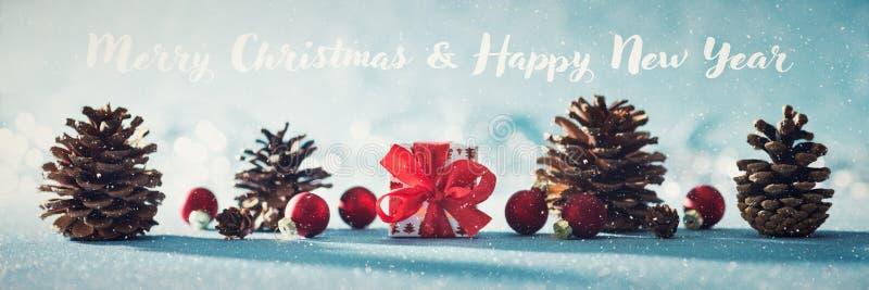 Schöne einfache Weihnachtsfahne mit Kopienraum Nettes Weihnachtsgeschenk, rote Verzierungen und Kiefernkegel auf glänzendem blaue lizenzfreies stockbild